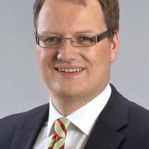 Porträtfoto von Olaf Schade vor grauem Hintergrund