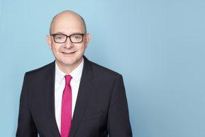 Porträtfoto von Andre Stinka vor hellblauem Hintergrund