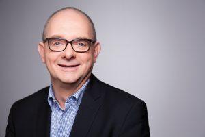 Porträtfoto von Andre Stinka vor grauem Hintergrund