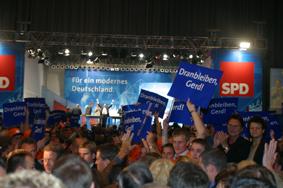 """Publikum mit Plakaten """"Dranbleiben Gerd"""" während der Wahlkampfveranstaltung in Dortmund am 20. 09. 02"""
