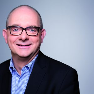 Portrait von André Stinka vor grauem Hintergrund