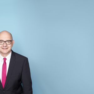 Portrait von Andre Stinka vor hellblauem Hintergrund