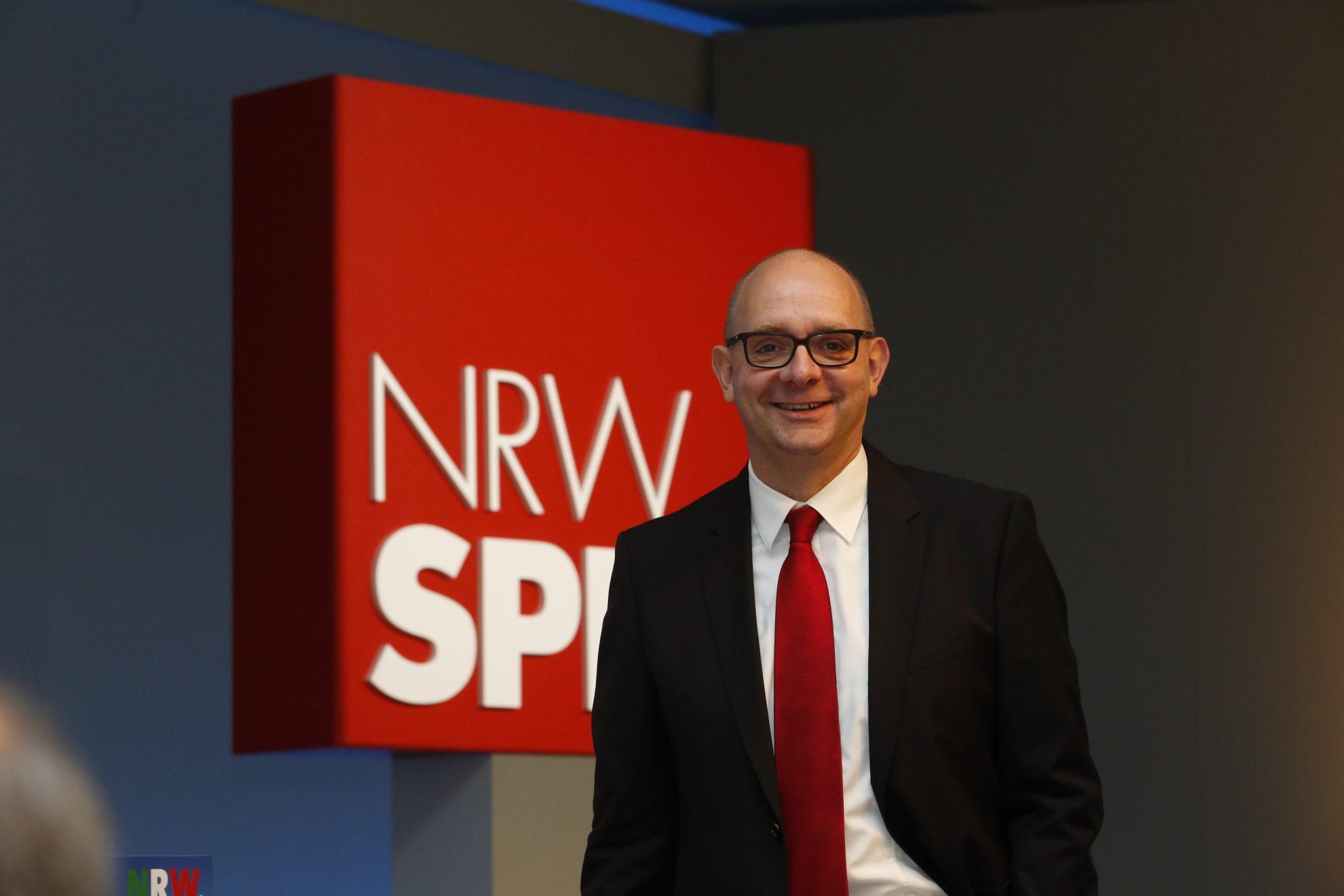 Andre Stinka vor dem Logo der NRWSPD