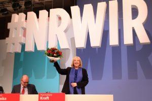 Hannelore Kraft steht lachend mit einem Blumenstrauß in der Hand auf dem Podium bei #NRWIR