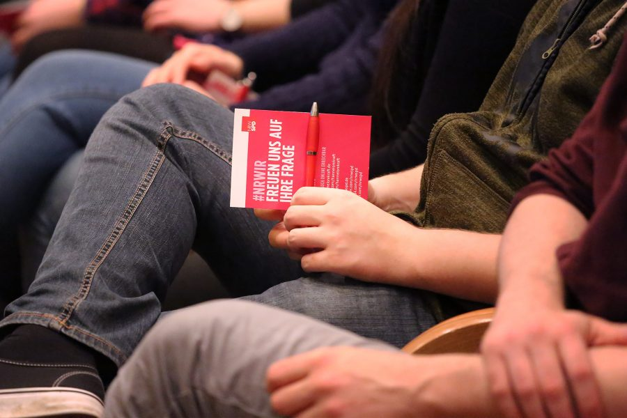 Eine Person sitzt und hält Flyer und Kuli der SPD in der Hand