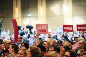 """Eine Frau hält umgeben von Menschen ein Plakat mit der Aufschrift """"Kraft für NRW"""" ein die Höhe"""