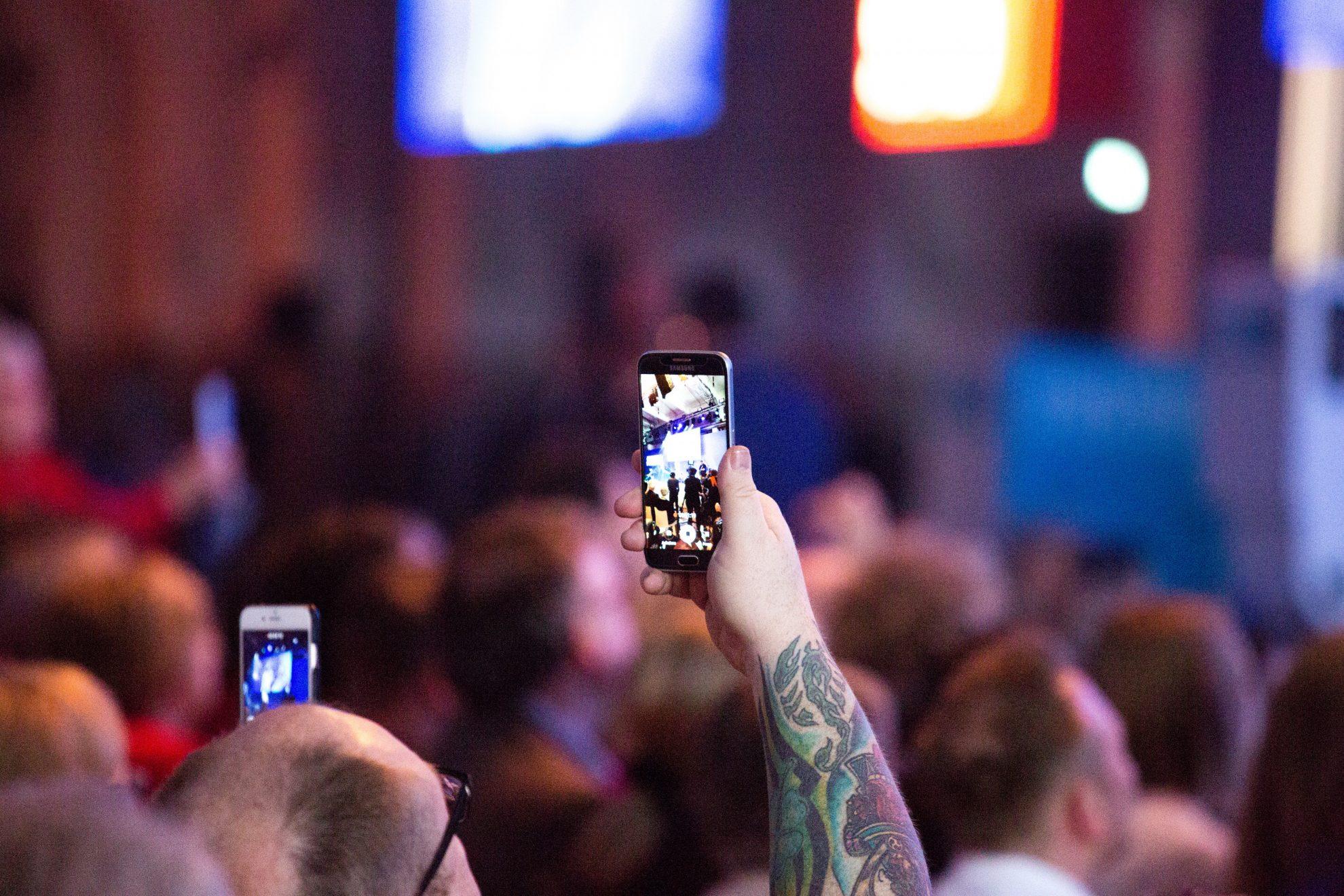Ein Mann fotografiert mit einem Handy den Wahlkampfauftakt