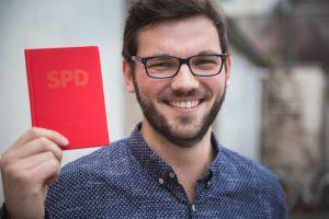 SPD-Neumitglied Marcel hält sein neues Parteibuch hoch und lächelt in die Kamera