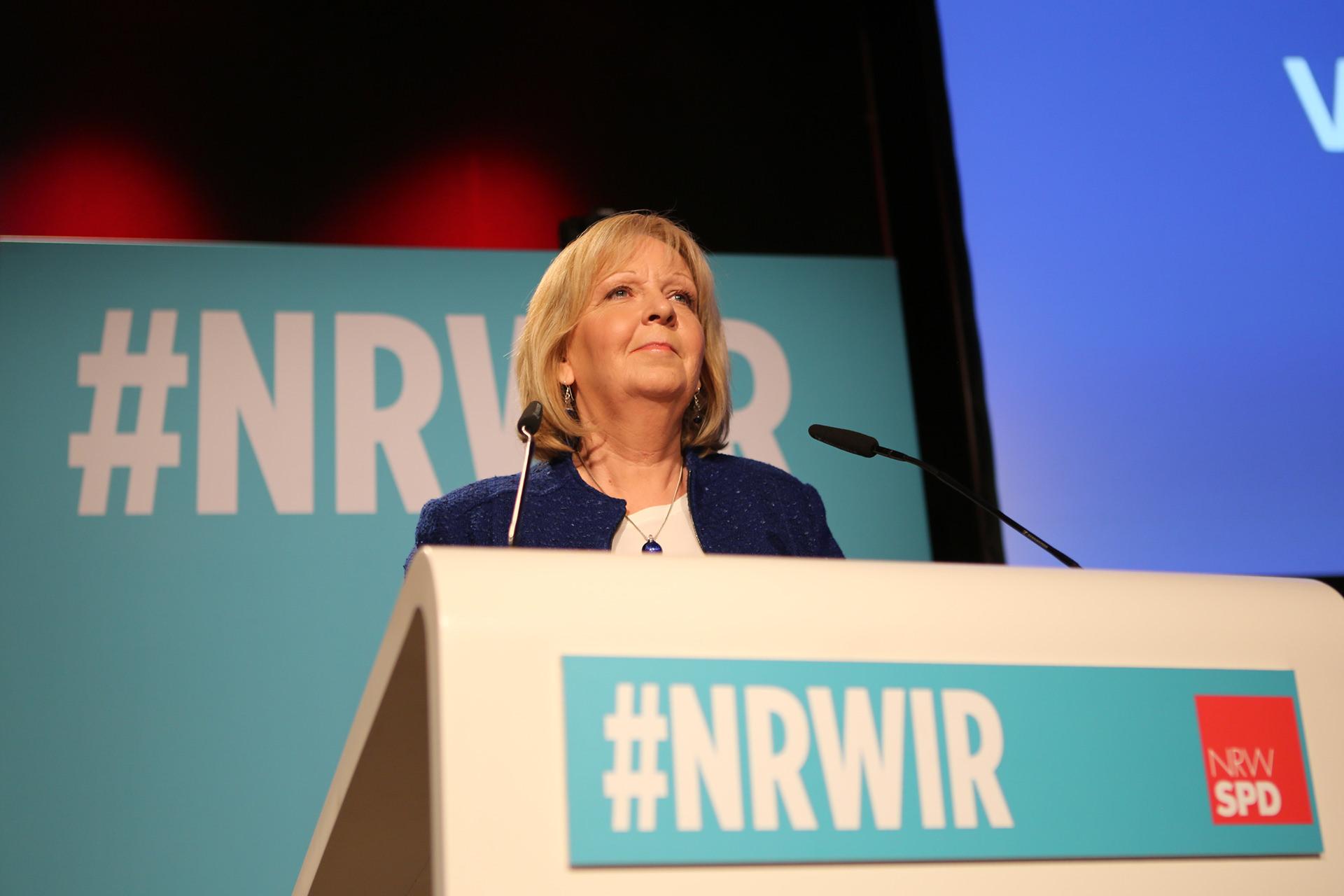 Hannelore Kraft bei einer Rede. Auf der Front des Pultes steht #NRWIR