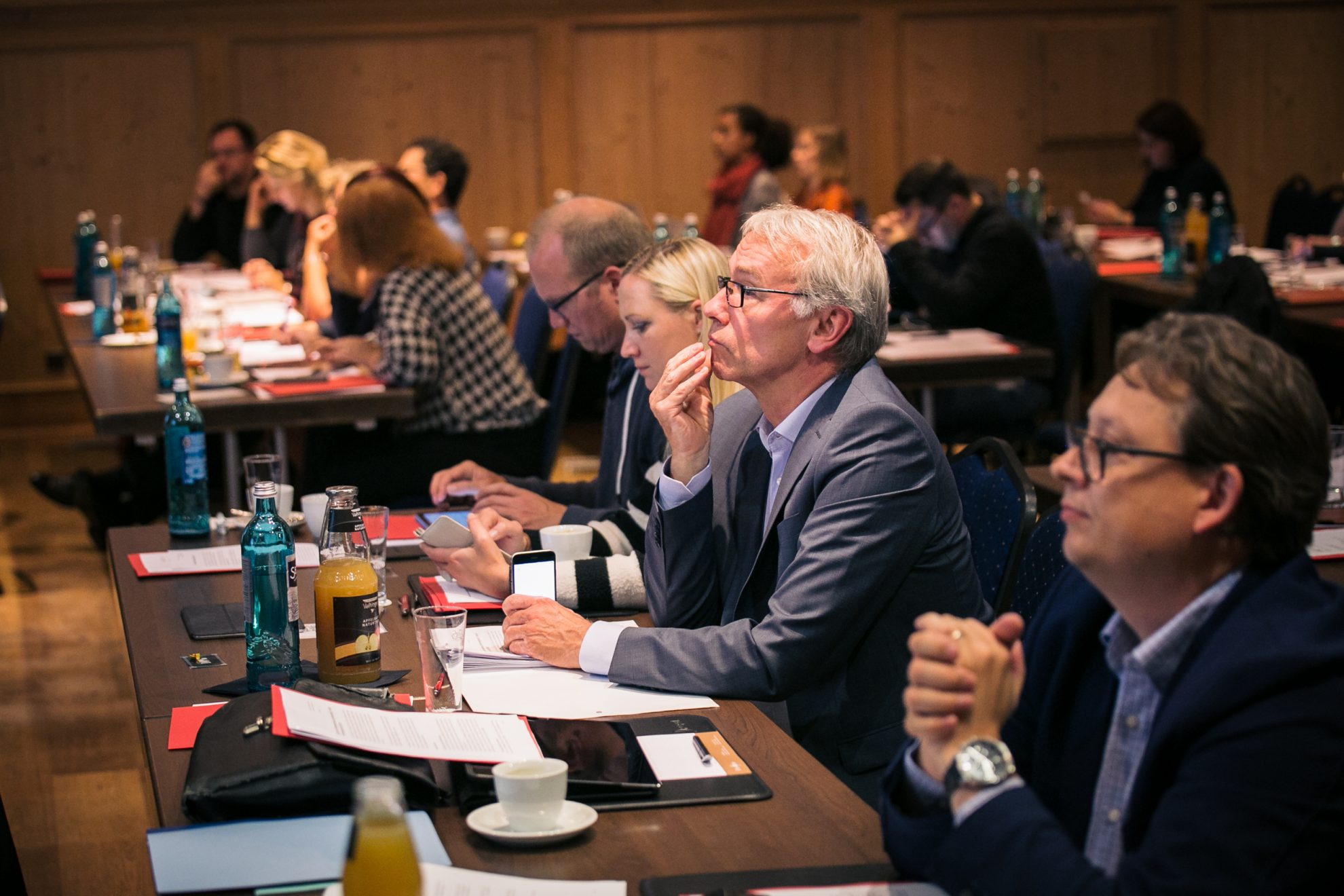 Teilnehmer der Klausur sitzen an den Tischen und folgen einer Rede