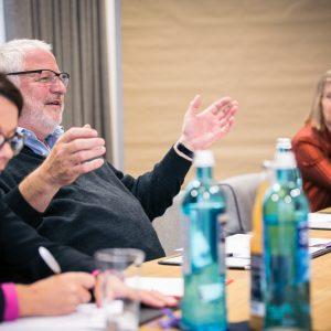 Mann spricht bei der Klausurtagung. Nadja Lüders schreibt im Vordergrund mit