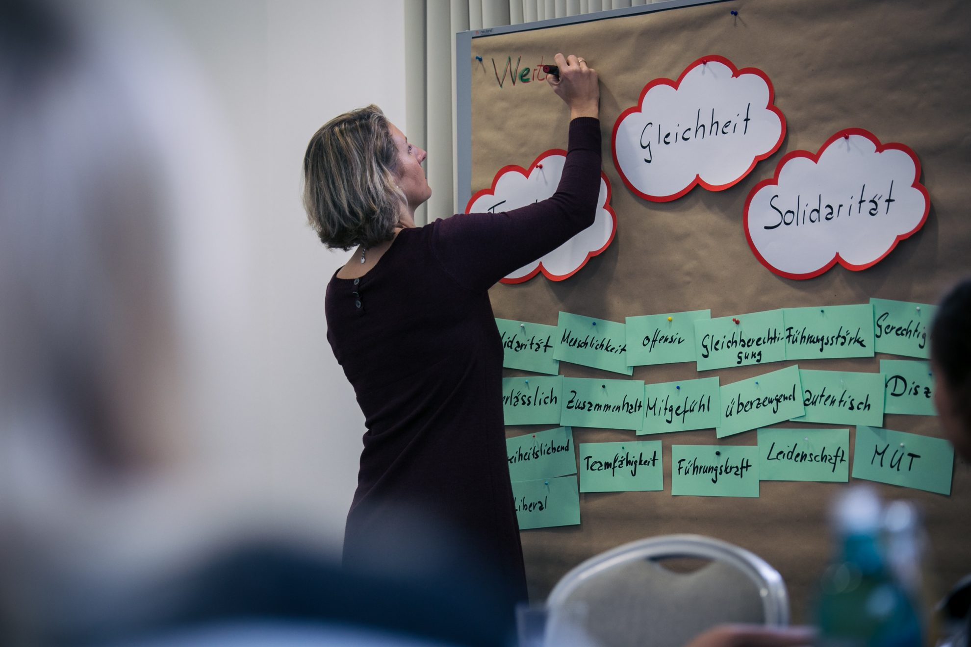"""Eine Teilnehmerin beschriftet ein Plakat mit den Überschriften """"Gleichheit"""" und """"Solidarität"""""""