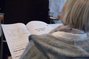 Eine Person liest Infomaterial beim Landesparteirat