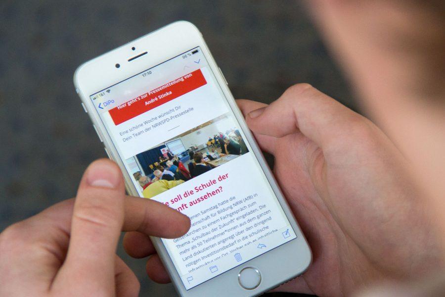 Ein Mann hält ein Handy und ist auf der Website der NRWSPD