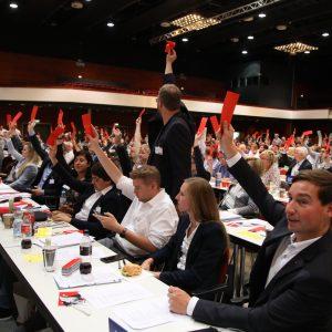 Sebastian Hartmann und andere Delegierte heben ihre Stimmkarten