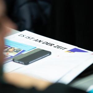 """Ein Handy liegt auf einem Flyer mit der Überschrift """"Es ist an der Zeit"""""""