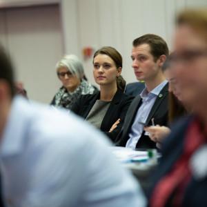 Teilnehmer bei der Veranstaltung folgen einer Rede