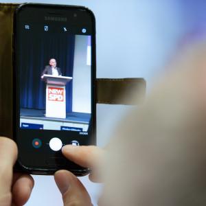 Ein Mann filmt die Rede von Norbert Walter-Borjans mit seinem Handy