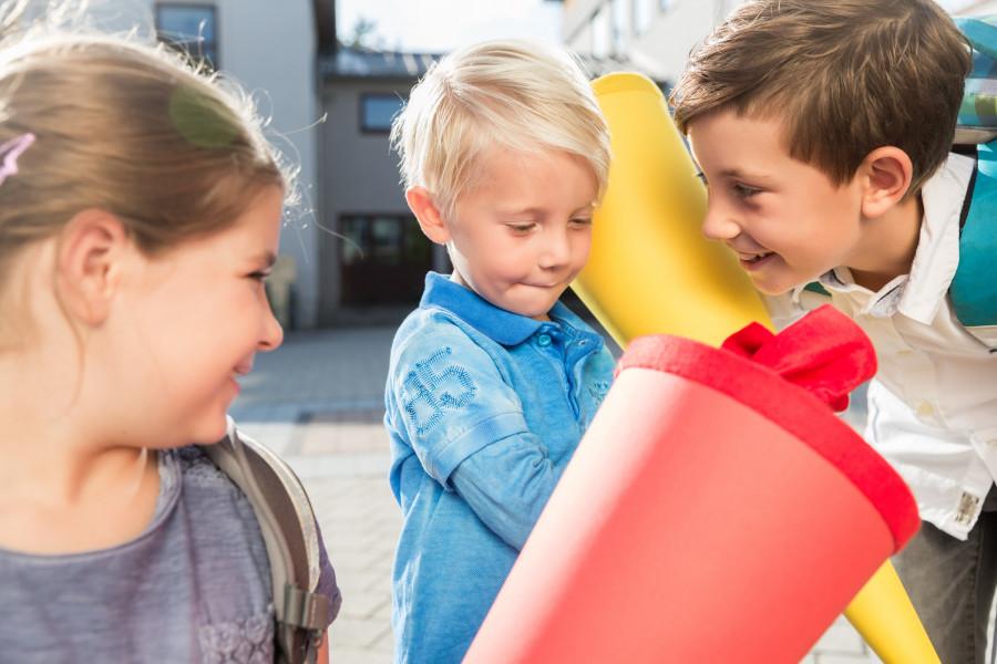 Foto: Kinder mit bunten Schultüten stehen vor einem Gebäude
