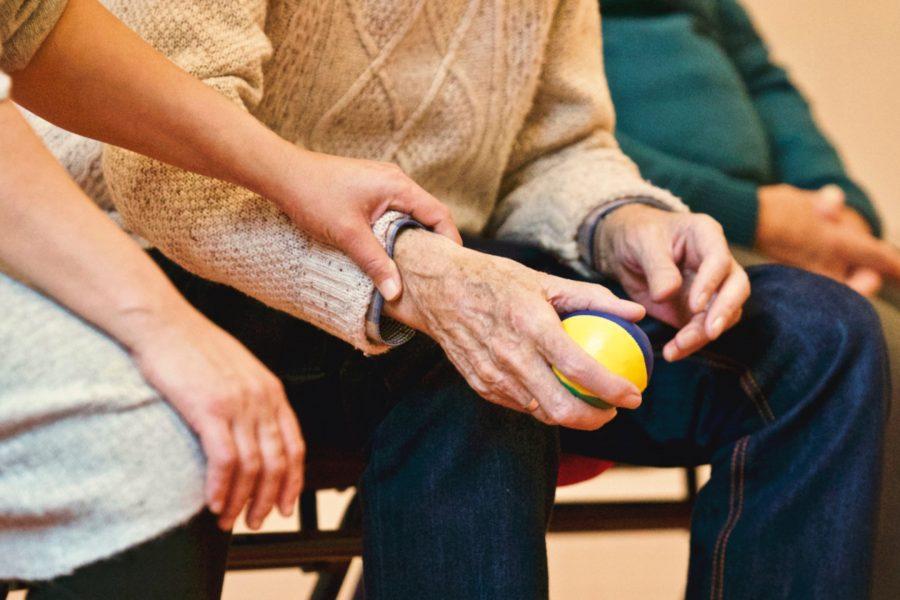 Der Arm einer älteren Person wird von einer Jüngeren gehalten.