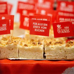 """Kuchen der Jusos bei der FunktionärInnenkonferenz in Essen mit kleinen beschrifteten Fähnchen wie """"Für alle ein Stück vom Kuchen"""" und """"NRW Jusos"""""""