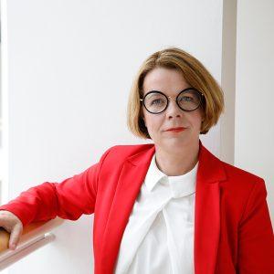 Porträtfoto von Anja Lüders. Ein Arm ist auf einem Geländer.