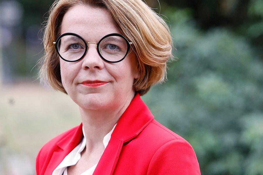 Porträtfoto von Nadja Lüders. Sie trägt ein weißes Hemd und ein rotes Jackett.