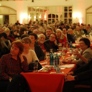 """Politischer Aschermittwoch im Saal der Traditionsgaststätte """"Freischütz"""" in Schwerte. Der Saal ist voll mit Menschen. Sie sitzen an langen Tafeln und schauen gebannt auf die Bühne und hören den Rednern zu."""