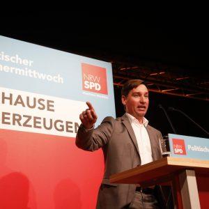 """Sebastian Hartmann steht am Rednerpult mit erhobener Hand. Im Hintergrund ein Aufsteller in Blau und Rot mit der Aufschrift Politischer Aschermittwoch und """"Zuhause überzeugen"""". Dem Slogan der bevorstehenden Kommunalwahl in NRW"""