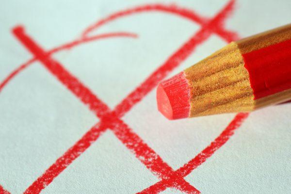 Roter Buntstift vor einem weißen Blatt Papier, auf dem ein roter Kreis mit einem roten Kreuz aufgemalt ist