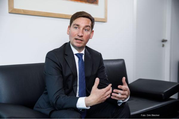 Sebastian Hartmann, NRWSPD-Vorsitzender, sitzt in einem dunklen Anzug gekleidet auf einer dunklen Couch, redet und bewegt dabei die Hände